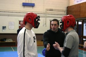 Jamie Clubb coaches two seminar students in a pre-emptive strike drill
